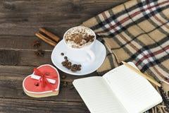 Чашка капучино, сердца сформировала сообщение ширины печений, тетрадь и checkered шотландку на коричневом деревянном столе стоковое фото