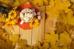 Чашка капучино с зефирами на салфетке, рядом с хризантемами на предпосылке листьев Стоковые Фото