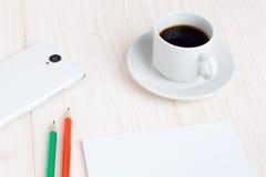 Чашка кофе, блокнот, карандаши, smartphone на таблице стоковые фотографии rf