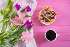 Чашка кофе, вафли с ягодами и нежный букет красивых тюльпанов на розовой деревянной предпосылке Стоковая Фотография RF