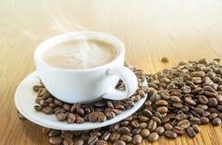 Чашка кофе в белой чашке и кофейных зернах на ба деревянного стола Стоковые Изображения RF
