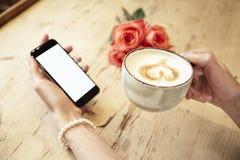 Чашка кофе в красивых руках женщины Дама используя интернет мобильного телефона в кафе Пустой экран для плана Behin цветков красн стоковое изображение