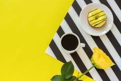 Чашка кофе, донут на плите и желтая роза на стильной черно-белой салфетке на желтой предпосылке Минимальный стиль Концепция хорош стоковые фотографии rf