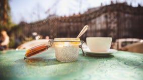Чашка кофе и десерт с семенами chia в стеклянном опарнике на таблице в кафе снаружи стоковые фото