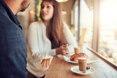 Чашка кофе и еда на таблице при пары говоря в кафе Стоковые Изображения RF