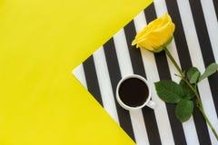 Чашка кофе и желтая роза на стильной черно-белой салфетке на желтой предпосылке Минимальный стиль Доброе утро или день концепции стоковое изображение