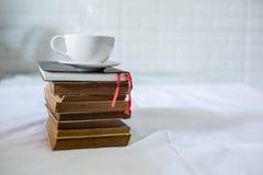 Чашка кофе и книга на кровати стоковая фотография