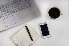 Чашка кофе и компьтер-книжка на белой таблице Стоковое фото RF