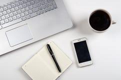 Чашка кофе и компьтер-книжка на белой таблице Стоковые Изображения RF