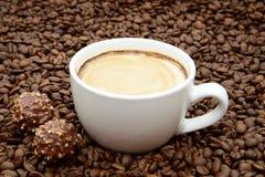 Чашка кофе и конфеты на предпосылке кофейных зерен Стоковая Фотография