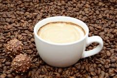 Чашка кофе и конфеты на предпосылке кофейных зерен Стоковое Изображение