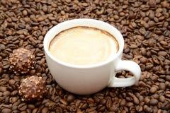 Чашка кофе и конфеты на предпосылке кофейных зерен Стоковые Изображения