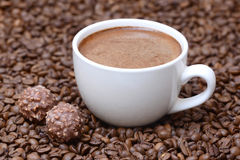 Чашка кофе и конфеты на предпосылке кофейных зерен Стоковые Изображения RF