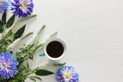 чашка кофе и красивое расположение голубых и белых цветков Стоковое Изображение