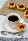 Чашка кофе и малые торты стоковые изображения