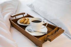 Чашка кофе и печенья в деревянном подносе на удобной кровати Стоковая Фотография RF