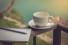 Чашка кофе и тетрадь стоя на балконе с предпосылкой озера Стоковые Изображения