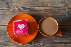 Чашка кофе и торт с сердцем на темном деревянном столе Стоковые Фотографии RF