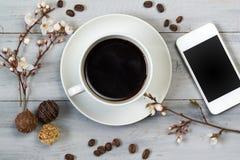 Чашка кофе и умный телефон, на деревянном столе с цветками вишни, конфетой шоколада и кофейными зернами, взгляд сверху Стоковое фото RF
