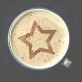Чашка кофе капучино с пеной в форме звезды на сини Стоковая Фотография RF