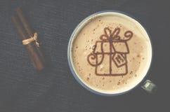 Чашка кофе капучино с пеной в форме подарка на голубом j Стоковые Фото