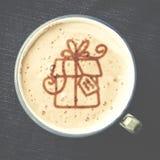 Чашка кофе капучино с пеной в форме подарка на сини Стоковое Изображение