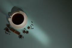Чашка кофе, кардамон, зерна кофе и циннамон на предпосылке бирюзы Стоковые Фотографии RF