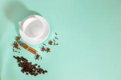 Чашка кофе, кардамон, зерна кофе и циннамон на предпосылке бирюзы Стоковые Изображения RF
