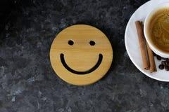 Чашка кофе ключ к хорошему настроению Деревянный smiley на темной, черной, текстурной предпосылке На крае вы можете увидеть белиз стоковые изображения rf