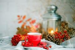 Чашка кофе, конусы, ягоды и листья осени на деревянном столе крупный план предпосылки осени красит красный цвет листьев плюща пом Стоковое Изображение RF
