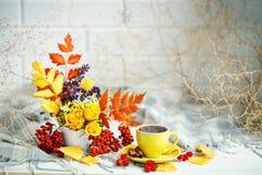 Чашка кофе, листья осени и цветки на деревянном столе жизнь осени все еще Селективный фокус Стоковое фото RF