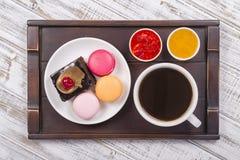 Чашка кофе, мед, варенье клубники, шоколадный торт части и торты macaron на подносе на белом деревянном столе Концепция образа жи Стоковое Изображение