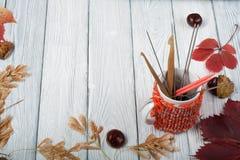 Чашка кофе натюрморта осени на деревянном столе nitted свитер с кружкой листьев осени, спиц, вязания крючком и кофе Стоковое Фото