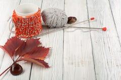 Чашка кофе натюрморта осени на деревянном столе nitted свитер с кружкой листьев осени, спиц, вязания крючком и кофе Стоковая Фотография RF