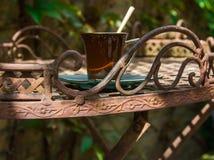 Чашка кофе на выкованной декоративной таблице в саде Стоковая Фотография RF