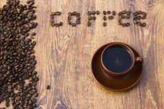 Чашка кофе на деревянной предпосылке с кофейными зернами Стоковые Изображения