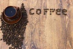 Чашка кофе на деревянной предпосылке с кофейными зернами Стоковое фото RF