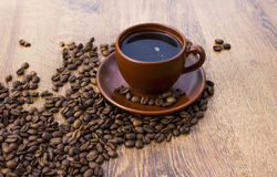 Чашка кофе на деревянной предпосылке с кофейными зернами Стоковые Фото