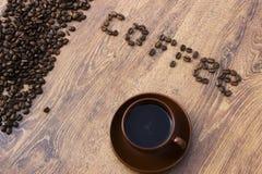 Чашка кофе на деревянной предпосылке с кофейными зернами Стоковая Фотография