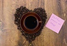 Чашка кофе на деревянной предпосылке с кофейными зернами Стоковая Фотография RF