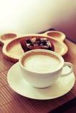 Чашка кофе на деревянном столе с плитой нерезкости пирожного на предпосылке Стоковые Изображения RF