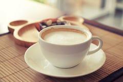Чашка кофе на деревянном столе с плитой нерезкости пирожного на предпосылке Стоковое Изображение RF