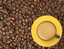Чашка кофе на кофейных зернах стоковое фото