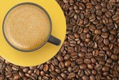 Чашка кофе на кофейных зернах стоковая фотография