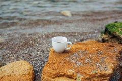 Чашка кофе на морской воде и предпосылке камня Концепция утра свежести моря Стоковое Изображение