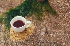 Чашка кофе на морской воде и предпосылке камня Концепция утра свежести моря Стоковая Фотография