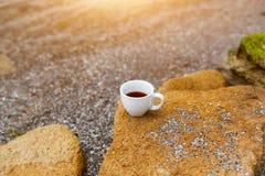 Чашка кофе на морской воде и предпосылке камня Концепция утра свежести моря Стоковое Фото