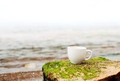 Чашка кофе на морской воде и предпосылке камня Концепция утра свежести моря Стоковые Изображения