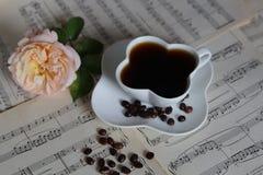 Чашка кофе на музыкальных листах с розой Стоковые Изображения