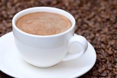 Чашка кофе на предпосылке кофейных зерен Стоковая Фотография